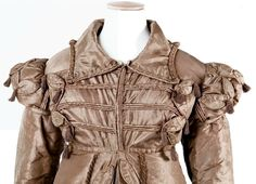 1818 - 1820 silk pelisse (detail) | A fawn silk carriage dress pelisse, with frogged front, Cap sleeves over long sleeves. Tasselled decorations.