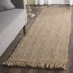 null An area rug is one of the easiest ways to warm up a space and add some character. Hand-woven in India of 100% jute and deliberately distressed with fringed edges, this understated beige rug will anchor any arrangement with artful appeal. Strategically place it in the foyer and use it as a conversation starter for guests and family members alike, or roll it out on your outdoor patio to take advantage of its superior durability and stain resistance. No matter where you decide to display…