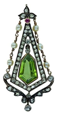 A beautiful pendant in silver over gold is designed around a wonderful faceted kite shape peridot. A geometric frame of rose-cut diamonds is enhanced with a matching diamond set garland below and a strand of natural oriental pearls on either side. A tiny ruby sits atop for good luck. A superb transitional Victorian-Edwardian jewel, circa 1900.