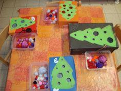 een schoendoos met een kerstboom op het deksel, gaatjes erin maken. De kleuters kunnen kiezen: de boom versieren (deksel onderaan zetten) of de balletjes in de juiste gaatjes stoppen (ervaren van verschillende maten)