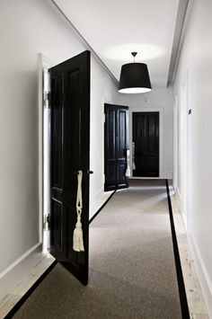 white tassel tiebacks hung on black doors By Malene Birger HQ, Copenhagen, Denmark