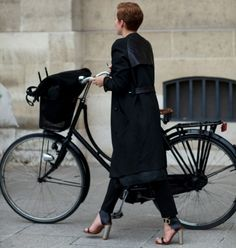 A black bicycle complements an all-black outfit. Who says you can't ride a bike in heels?