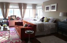 Putting a couch at the foot of a bed helps to divide a studio apartment into separate living areas.