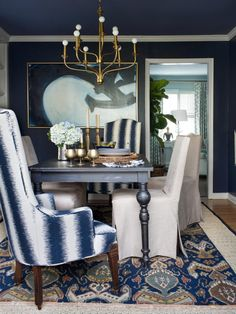 Blue Stain Wall Come With Beige Fabric Area Rug And Gold Stain Ceiling Lamp Plus Varnished Dark Wood Dining Table Together With Varnished Wood Floor Tile And Also White Fabric Chair Cover Plus Striped Pattern Blue And White Fabric Armchair