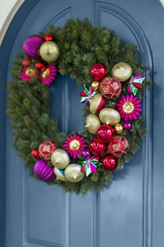 a jewel toned ornament trimmed wreath beckons guests with vibrant christmas style