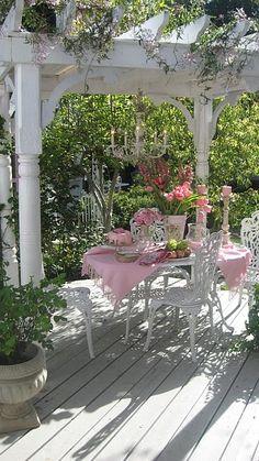 Comer al fresco. Mesa y sillas blancas con decoración en tonos rosa, colocada en un cenador de madera también blanca. Sensación de frescor, inspiración romántica; un lugar perfecto para comer o cenar en primavera y verano.Imágen vía Cndy Ellis Art blog