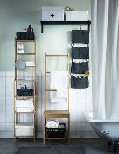Bilde av et baderom med et badekar og oppbevaring som hyller, flettede kurver og plastbeholdere.