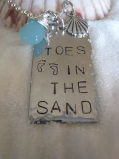 Toes in the Sand Hand Stamped  Rectangular Hammered Pendant with Blue Sea Glass and Silver Charms. $24.99, via Etsy.