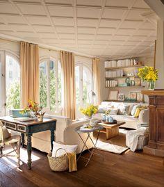 Salón con tres grandes ventanales, dos sofás enfrentados y un rincón de trabajo