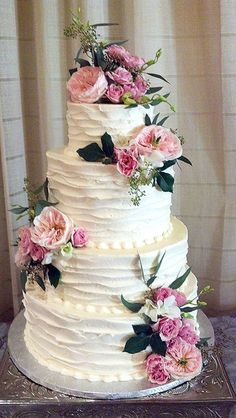 Rustic country old-fashioned buttercream wedding cake with pink flowers.