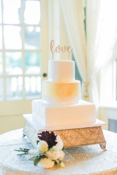 'Love' topped classic white wedding cake: Photography: Rhythm Photography - rhythm-photography.com   Read More on SMP: http://stylemepretty.com/vault/gallery/68178