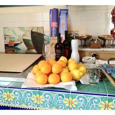 Tripudio di prodotti tipici: arance e limoni su cucina con piastrelle in ceramica di Vietri sul Mare #localproducts #madeinitaly #italianfruits