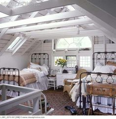 the riding boots are over the top but I love those iron bed frames, absent the fussy linens.