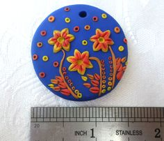 Polymer clay pendant, handmade with applique technique, one of a kind. Blue, with yellow, red and orange flowers, leaves and dots. By Lis Shteindel.