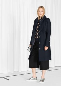 A long wool-blend trench coat with a classic and elegant form.