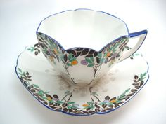 Beautiful Art Deco tea cup and saucer from Shelley.  Shape: Queen Anne  Handpainted black trees withorange, blue and lilac fruits. Grey daisies and grass on the bottom of the cup and the center of the saucer.  The rim of the tea cup and the saucer are royal blue.  C. 1925 - 1945  Cup measures: 2 1/4 high & Saucer measures 5 3/4 across  Very good conditon, no chips, no cracks, no crazing, no hairlines, no stains and both pieces ping beautifully.  I try to show the true colors in my pictures…