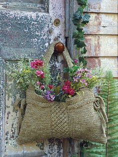 Use an old handbag or slingbag/basket, fill with container and flowers and hang on outside doors for welcome...
