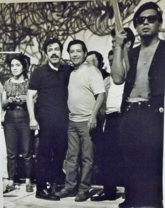 From left to right: Dolores Huerta, Rodolfo 'Corky' Gonzales, Cesar Chavez. A member of the Brown Berets stands in the foreground. - Photo credit: Gilberto Martinez.