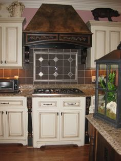 """Epoxy sculpted relief carvings were created by the artist to add interest to this range hood and lower cabinet columns.  The hood was then fauxed with dark brown/black and copper to coordinate with the pre-existing copper faux """"roof""""."""