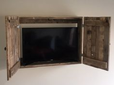 Handcrafted wall-mount TV cabinet made from repurposed pallet wood. Notches in shelf allow for cables to run through without difficulty. Also