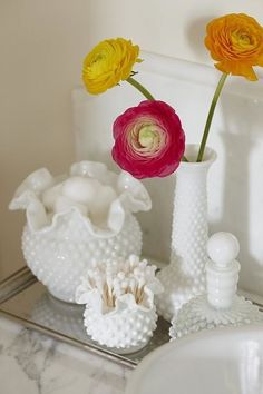 Designer Sarah Richardson grouped milk glass containers in varying heights on a mirrored tray to display cotton balls and swabs.