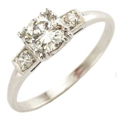 Beauty Mark: A classic solitaire featuring a brilliant center diamond is made even better with well placed accents. Two little side diamonds in crisp square milgrain frames make the whole design pop with a fresh bright feel. Ca.1950. Maloys.com