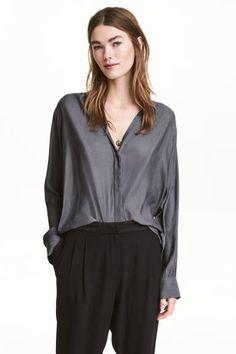 Blusa com decote em V: Blusa de mangas compridas em tecido delicado. Modelo com decote em V, botões ocultos na frente e botões de madrepérola nos punhos. Base arredondada e ligeiramente mais comprida atrás.