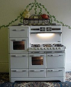 "60"" O'Keefe & Merritt Antique Gas Stove  Chrome stove top 6 burners with simmers, warming oven, upper left side oven, left side broiler, center oven,  right side Grillevator broiler, clock/timer, 1 power outlet, fluorescent back splash light  with chrome shelf, 2 pots & pan storage on bottom left & right"