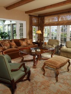 Attractive room with  rust, browns and tan colors mostly, all very well blended - the red-rust colors and green in the leather chair adding some pop to the otherwise earth tone scheme. Woven blinds and rug with color coordinated draperies are also a nice touch.