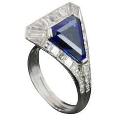 Art Deco Unusual Sculptural Sapphire Diamond Cluster Ring. Sculptural art deco ring centering on a large triangular-cut Ceylon sapphire with a diamond surround European circa 1930s  1 triangular-cut sapphire 4.52cts accompanied by an SSEF certificate stating that the stone is a natural unheated Ceylon sapphire 31 calibré-cut diamonds 1.13cts approx. Platinum
