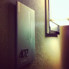 Guestroom graphics were developed to reflect the renovated look of the Hilton Atlanta Airport Hotel. By using a satin finished metal, simple geometric pattern, etching, and polished detail the signage embodies a modern yet elegant look.Created with Hirs& Door Signage, Hotel Signage, Wayfinding Signage, Signage Design, Environmental Graphics, Environmental Design, Atlanta Airport, Airport Hotel, Ada Signs