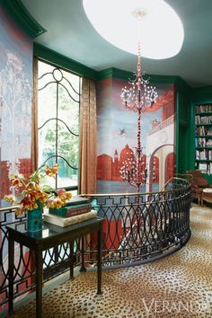 The main entry is on the middle level of the house, therefore necessitating a grand stroll down a sweeping circular staircase to the large open living room.  Bookshelves on the landing define an intimate reading nook. Chandelier, Tony Duquette for Remains Lighting.   - Veranda.com