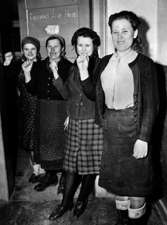 Russian forced laborers, freed by US troops in the Rhineland-Palatinate, give the communist salute for the photographer as they pose outside their room. The room door bears the hand-written warning: RUSSIANS LIVE HERE! The Germans forced an estimated 12 million people from 20 different countries to become slaves in their industrial plants; 2/3 of the slave labor came from eastern European countries.