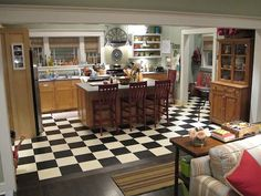 The kitchen, living, and dining room flow into each other, building a family-friendly space. Black and white checker tiles create graphic interest.