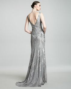 Monique Lhuillier returns to the decadent 1920s to find inspiration for this ornately embroidered gown. Silver chiffon with allover Art Deco crystal embroidery.