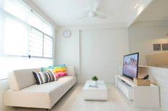 Sala minimalista clara, com detalhes coloridos.