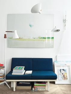 Aumas outfitted a vintage steel-frame sofa by George Nelson in navy blue fabric from Kvadrat and hung one of his own photos just above it. The lamp to the left of the sofa is a 1960s design found at a Lisbon flea market, and to the right of the sofa is a Two-Arms rotating sconce by the mid-century French designer Serge Mouille.