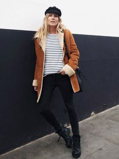 Blogger Lucy Williams wearing a shearling coat, breton top, black skinny jeans and a baker boy cap.