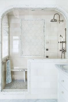 Timeless style comes together with chrome, marble and cool whites in a coastal home's master bathroom. Skip a traditional shower door or curtain for a sleeker look (and easier cleaning).