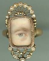 1790 English Georgian Miniature Lovers Eye of a Gentleman set in gold and Seed pearl ring. Size of ring is approx. size 5 and ring is approx. 1 inch by 1/2 inch. It has been years since I have had an eye in a ring. The painting is superb. Left blue eye of a gentleman with strong eyebrow and a touch of red in the corner which is always a sign of a well painted piece. Set in high karat gold with top and bottom crowns of seed pearls. Original glass covering.