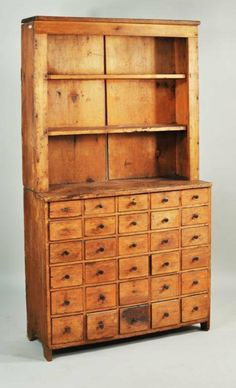 "American country pine apothecary cupboard in two pieces, open shelf top above 30 drawer apothecary base, early 19th C. 73 1/2"" high, 39 1/2"" wide, 16 1/2"" deep"