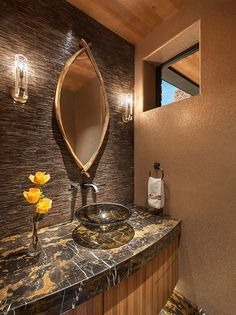 Shimmering powder room with marble floor and counter top, zebrawood cabinets, oval mirror and glass vessel sink. lighting by Jonathan Browning. Vessel sink and wall mounted faucet. Glass tile wall. Gold glass bead wallpaper | Susan Hersker, ASID - Interior Designer of Arizona #interiordesign #bathroom