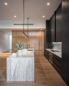 cuisine au design contemporain avec meubles noirs ilot central et plan de travail en marbre