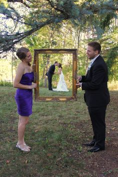 Bride and groom in picture framed being held by maid of honor and best man.
