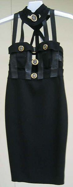 Black wool/silk dress with black leather straps and coin medallions, by Gianni Versace, Italian, fall/winter 1992-93.