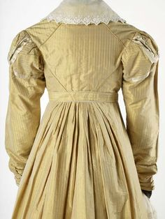 Dress | Museum of London Yellow striped silk dress with a high waist marked by belt. Puff sleeves with epaulettes of the same material. Skirt is pleated at sides and back and with padded decoration at hem. The silk is good quality, possibly a lustring type. The width is closer to French than English silks. Production Date: 1820-1824