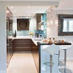 Small kitchen with black cabinetry, white worktops and white breakfast bar stools