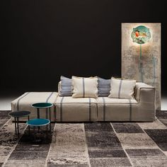 The Post Composition 3 sofa is a three-seater sofa composed of a one-armed chair, one chair and an ottoman, enriched by two decorative cushions.