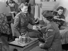 Trainee members of the Auxiliary Territorial Service Motor Transport Company relax in the rest room at the ATS MTC Training Centre, probably at Camberley. Two women enjoy a cup of tea, whilst a third eats a biscuit as she reads, and a fourth, in the background, is sewing and appears to be darning a sock. 1941.