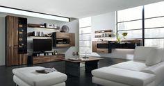 Futuristische Architektur gemixt mit natürlichen Materialien: Das erzeugt Spannung und Dynamik im Raum! Elegantes Schwarz kombiniert mit nussbraunen Holzelementen wird zum Blickfang und lässt den Raum edel und modern wirken. Die weiße Ledercouch ergänzt die luxuriöse Wohnraumgestaltung und lässt Gemütlichkeit aufkommen. Der schwarze Steinfußboden wird zum Highlight und steht im perfekten Kontrast zu den großflächigen Tageslichtfenstern, die viel Licht und Wärme in das erstklassige Ambiente…
